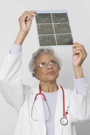 Senior medical practitioner examines xray Stock Photo - 12738048