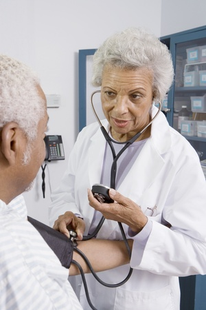 Senior medical practitioner takes blood pressure Stock Photo - 12738051