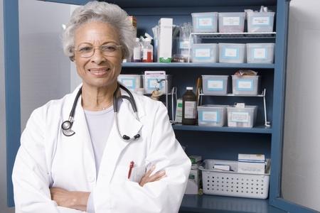 Portrait of senior medical practitioner and medicine cabinet Stock Photo - 12738062