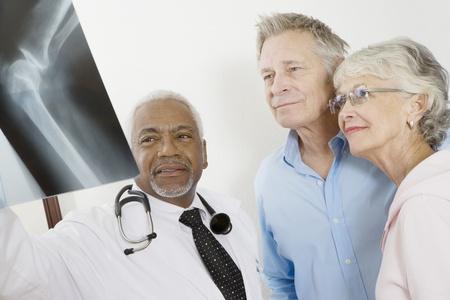 knees up: Senior medical practitioner explains xray to senior couple