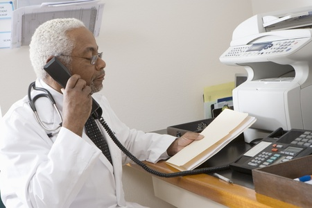 Senior medical practitioner on phone with hospital records Stock Photo - 12738067