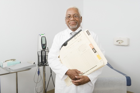 Senior healthcare professional stands with medical records Stock Photo - 12738082