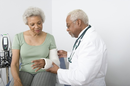 brazo roto: Profesional superior se ajusta yeso en el brazo roto