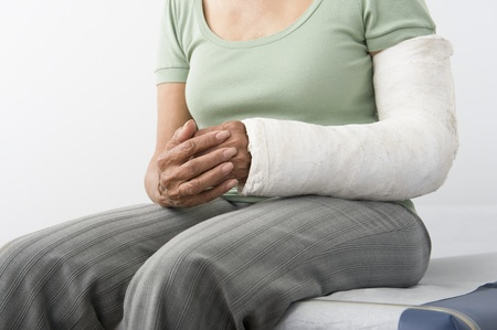 Senior woman sits with plastercast on broken arm mid-section Stock Photo - 12738089
