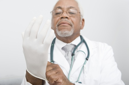 Senior practitioner pulls on surgical gloves Stock Photo - 12738090