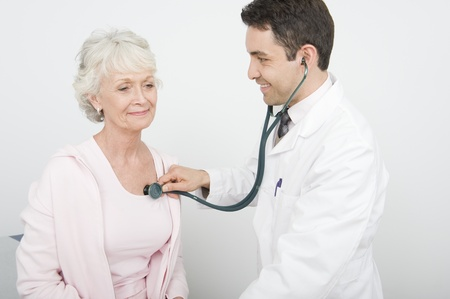 Mid adult doctor checks breathing of senior patient Stock Photo - 12738095