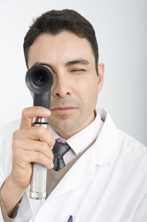Optician looks through sight testing equipment Stock Photo - 12738097