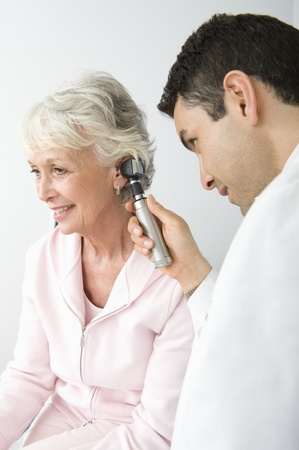 hearing: Mid adult doctor examining senior patient