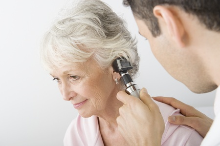 doctor examining woman: Mid adult doctor examining senior patient