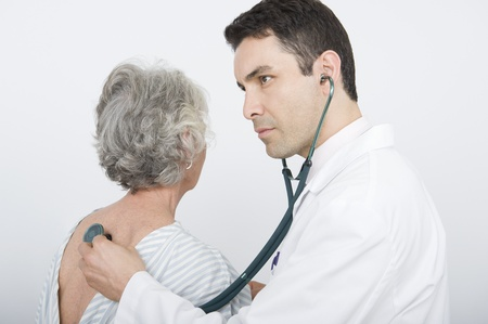 Mid adult doctor checks breathing of senior patient Stock Photo - 12738100