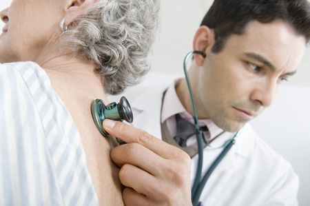 Mid adult doctor checks breathing of senior patient Stock Photo - 12738101