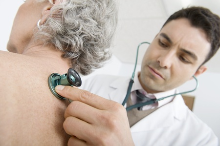Mid adult doctor checks breathing of senior patient Stock Photo - 12738102