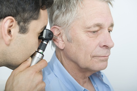 Mid adult doctor checks hearing of senior patient Stock Photo