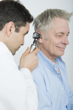 Mid adult doctor checks hearing of senior patient Stock Photo - 12738105