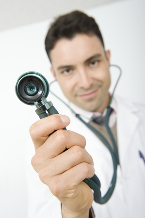 Mid adult doctor smiling and holding stethoscope Stock Photo - 12738107