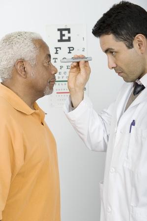Mid adult doctor examines senior man's eyesight Stock Photo - 12738108