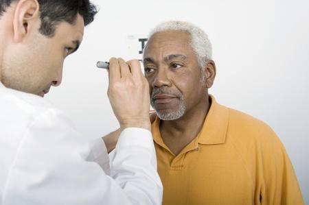 mid adult: Mid adult doctor examines senior mans eyesight LANG_EVOIMAGES