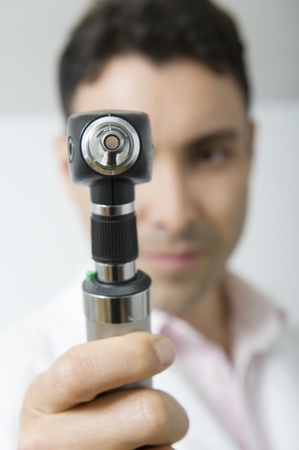 Mid adult doctor looks through sight testing equipment Stock Photo - 12738110