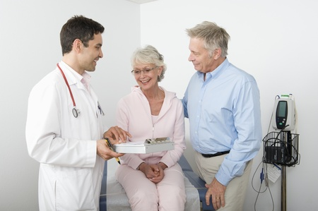 Mid adult doctor explains test results to senior couple Stock Photo