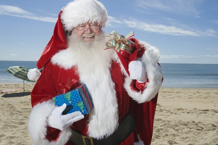 Father Christmas stands with his sack on a beach Stock Photo - 12738129