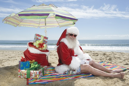 Father Christmas sits under a parasol on the beach Stock Photo - 12738130
