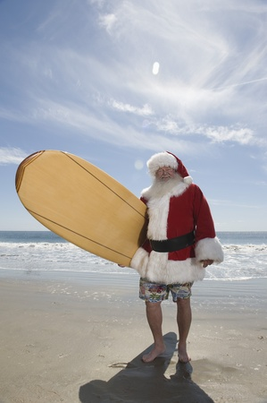 inappropriate: Father Christmas stands with a surfboard at the beach LANG_EVOIMAGES