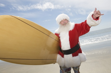 Father Christmas stands with a surfboard at the beach Stock Photo - 12738132
