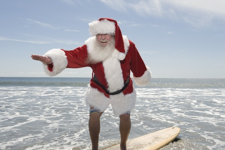waters  edge: Father Christmas surfboards at the waters edge