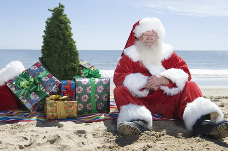 beach clothes: Father Christmas sits on the beach with a tree and presents