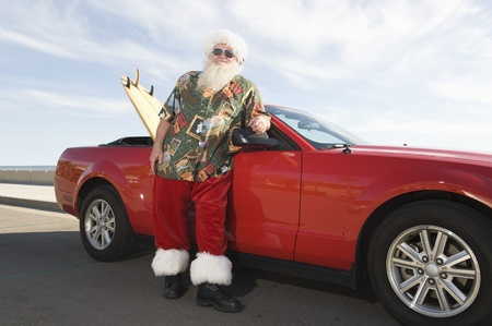 Father Christmas stands by red convertible with surfboard Stock Photo - 12738140