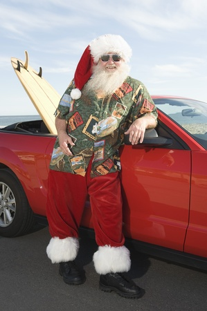 Father Christmas stands by red convertible with surfboard Stock Photo - 12738141