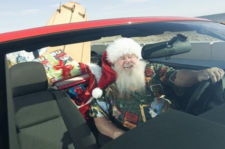 weihnachtsmann lustig: Der Weihnachtsmann sitzt im roten Cabrio mit Surfbrett