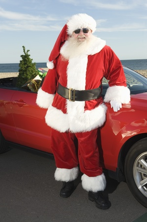 Father Christmas stands by red convertible with Christmas tree Stock Photo - 12738143