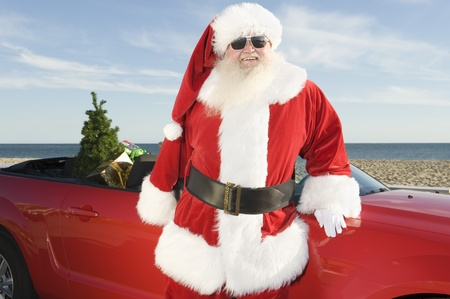 fake christmas tree: Father Christmas stands by red convertible with Christmas tree
