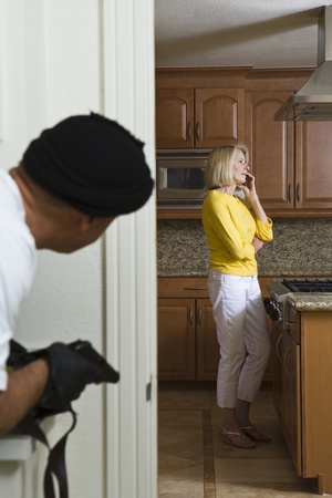 criminal activity: Burglar holding gun approaches woman on phone in kitchen LANG_EVOIMAGES