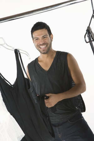 clothes rail: Wardobe stylist stands with clothes rail smiling
