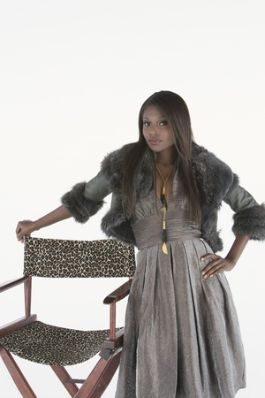 prima donna: Fashion model stands leaning on directors chair