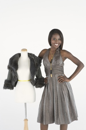 halterneck: Fashion model stands beside tailors dummy with fake fur bolero jacket