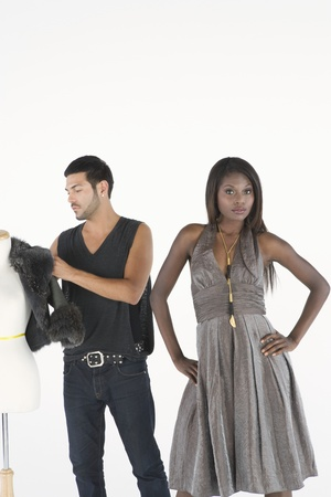 halterneck: Fashion stylist adjusts jacket on mannequin while model stands with hands on hips