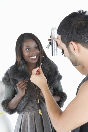 Hair stylist makes adjustments to model in fake fur jacket Stock Photo - 12738177