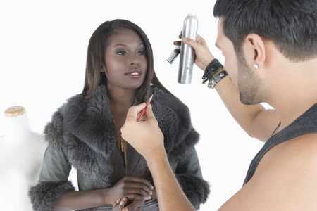 Hair stylist makes adjustments to model in fake fur jacket Stock Photo - 12738178