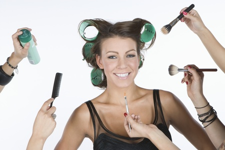 beautycare: Woman in rollers  with cosmetics products on hand