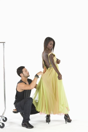 undone: Stylist adjusts dress in fitting LANG_EVOIMAGES
