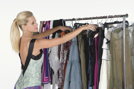 clothes rail: Woman chooses from a selection of items on a clothes rail LANG_EVOIMAGES