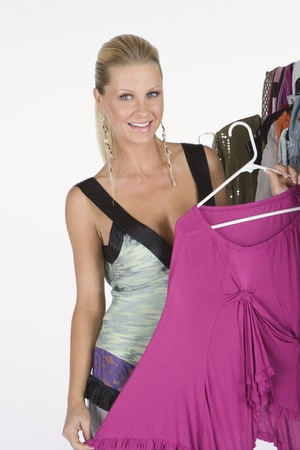 Woman chooses a pink blouse from a selection of items on a clothes rail Stock Photo - 12738207