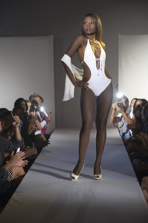 Woman in white swimwear stands on fashion catwalk