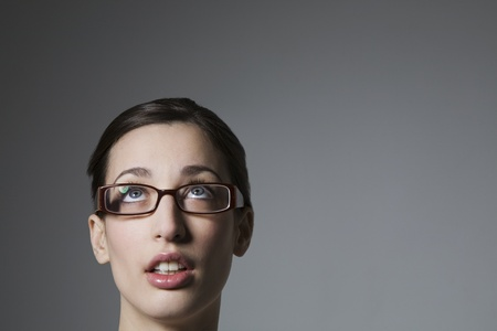 Brunette with blue eyes and spectacles looking up Stock Photo - 12738247
