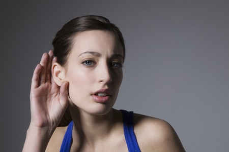quirky: Brunette with hand behind ear LANG_EVOIMAGES
