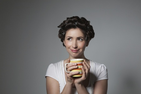 Coy young woman with hair curlers holding cup Stock Photo - 12738254
