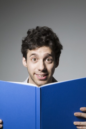 Young man smiling over book cover Stock Photo - 12738255